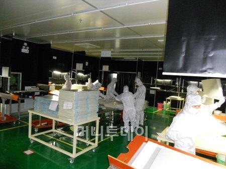 지난달 31일 신화인터텍 중국 동관 법인에서 작업자들이 광학필름의 품질을 확인하는 검사 공정을 진행하고 있다.