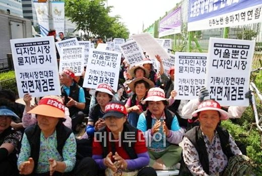 ↑가락시장 노점상 상인들이 지난 16일 가락시장 시설 현대화 사업에 반대해 시장에서 시위를 벌이고 있다. 사진=민주노점상전국연합(민주노련) 제공