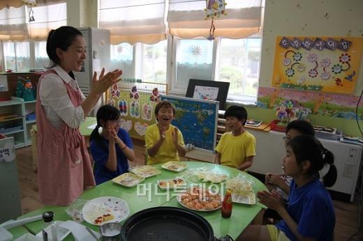 ↑한국외식산업연구소의 강버들 연구원(맨 왼쪽)은 칠보초 아이들에게 주먹밥 만드는 법을 가르쳤다. ⓒ하하야