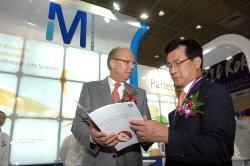 ↑ 바이오코리아 2011 전시회에서 유르겐 쾨닉 한국 머크 대표(왼쪽)가 이시종 충청북도 도지사(오른쪽)에게 머크의 바이오테크 제품과 서비스를 소개하고 있다. <br />
