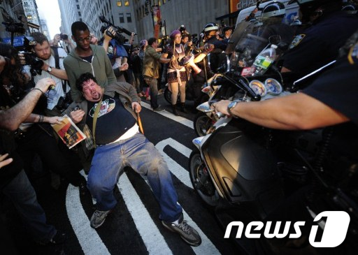 14일(현지시간) 미국 뉴욕 월가 인근에서 '월가를 점령하라' 시위 참여자가 경찰 오토바이 앞에 드러눕고 있다. (사진=AFP)  News1