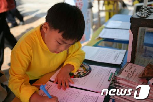 한 어린이가 인화학교 사태해결을 촉구하는 서명을 하고 있다. /사진제공=인화학교 성폭력대책위  News1
