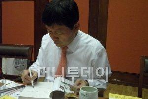 """김영식 천호식품 회장이 자신의 저서 """"10미터만 더 뛰어봐!""""에 사인하고 있다."""