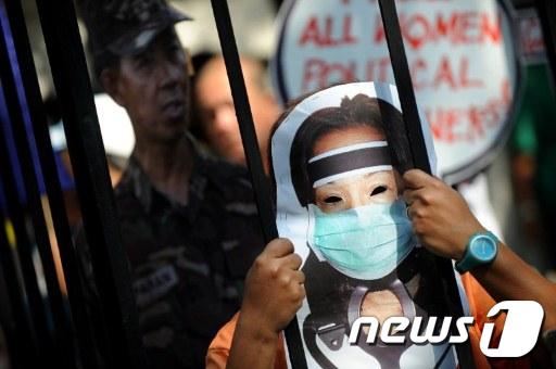 필리핀의 한 시위자가 지난달 신병 치료를 이유로 출국을 시도했던 아로요 전 대통령과 비슷한 가면을 쓴 채 아로요에 대한 처벌을 요구하고 있다.  AFP=News1