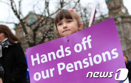 11월 30일 영국북아일랜드의 수도 벨파스트의 시청 관장에서 아이가 전면 파업 옹호 피켓을 들고 있다. AFP=News1