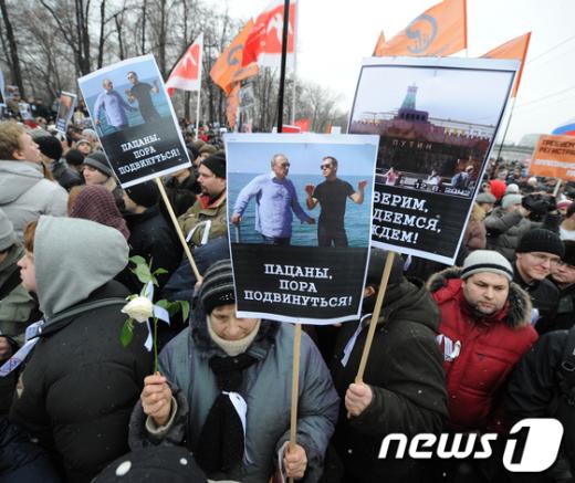 """10일 러시아 모스크바에서 부정선거 규탄 시위자들이 """"소년이여, 이제 그만 돌아갈 시간이야""""(왼쪽)와 """"우리는 희망과 기대가 있다고 믿는다!""""는 피켓을 들고 시위하고 있다. AFP=News1"""