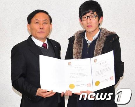 이상열 조선대 총장 직무대리(왼쪽)가 2일 강도를 붙잡은 김세훈 씨에게 모범상을 수여하고 있다. /사지제공=조선대  News1