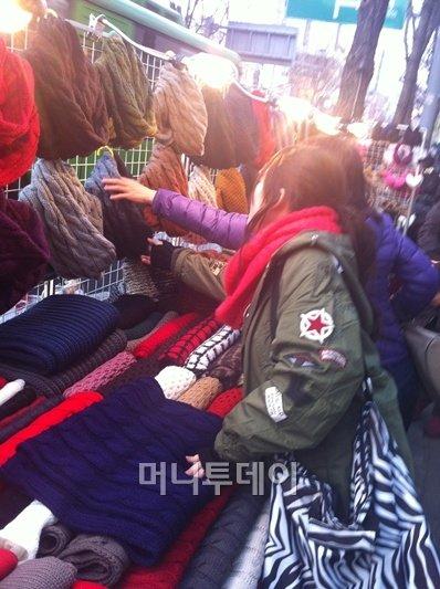 서울의 한 길거리에 있는 상점에서 목도리를 구입하는 두 사람