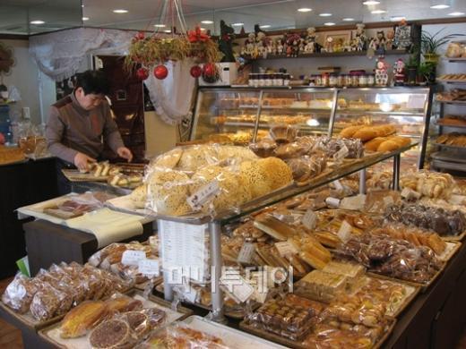 ↑효자베이커리의 유재영 사장이 진열대에 빵을 채우고 있는 모습
