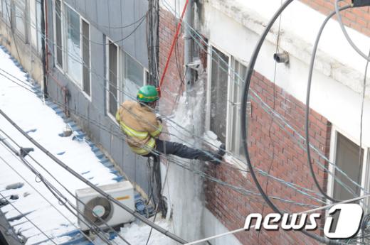 119소방요원이 주택가 배수로에 발생한 고드름을 제거하고 있다./사진제공=서울시청 News1