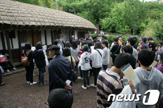 작가의 산책길' 탐방객들이 이중섭이 살았던 초가집을 둘러보고 있다. /사진제공=서귀포시청  News1