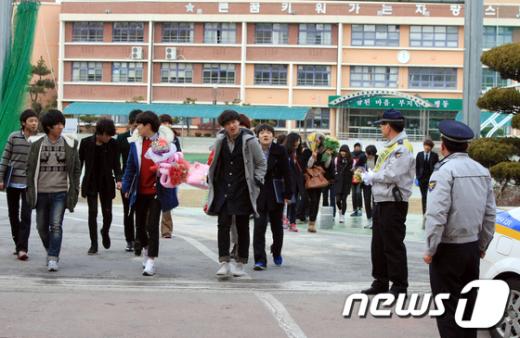 7일 졸업식이 열린 광주 동구 충장중학교에서 경찰관들이 교문을 나서는 학생들을 주시하고 있다.  News1 김태성 기자