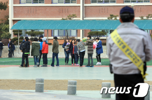 <br /> 7일 졸업식이 열린 광주 동구 충장중학교에서 한 경찰관이 뒤풀이를 하는 학생들을 살펴보고 있다.  News1 김태성 기자<br />