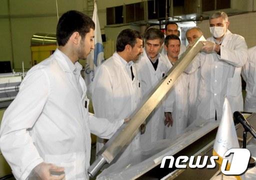 지난 15일 이란 테헤란의 연구용원자로센터에서 자체 제작한 3000개의 원심분리기를 살펴보고 있는 마무드 아마디네자드 대통령(왼쪽에서 두번째)과 연구진  AFP=News1