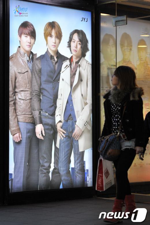 일본인 여성 관광객이 한국 인기 스타 JYJ의 광고판을 지나가고 있다. AFP=News1