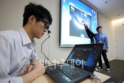 ↑삼성전자 직원들이 23일 장애인용 안구마우스 '아이캔'을 시연해 보이고 있다.