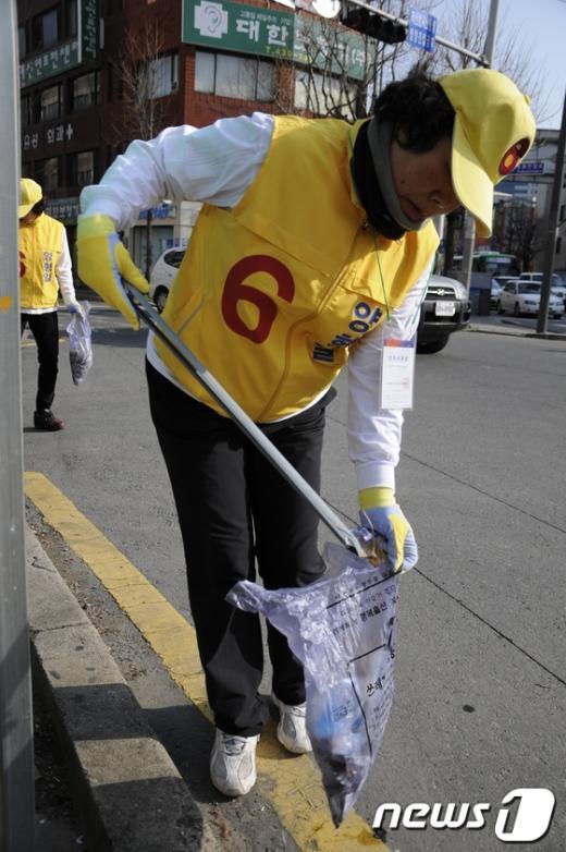 양형일 후보 선거사무원이 동구 거리에서 쓰레기를 줍고 있다.  News1