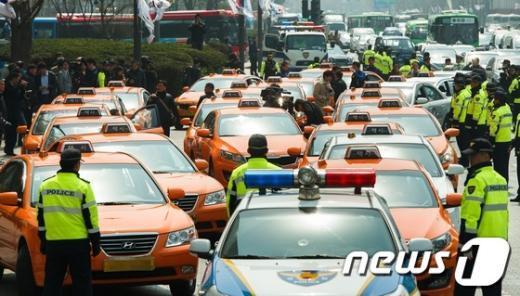 서울 법인택시들이 4일 정오광화문에서 LPG 가격 인하를 촉구하며 저속 운행에 나서자 경찰들이 막아서고 있다. News1 유승관 기자