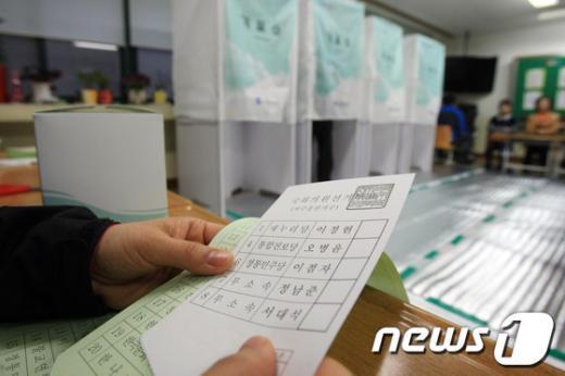 제19대 국회의원선거날인 11일 오전  광주 서구 금호2동 동명중학교 마련된 제4투표소에서 유권자들이 투표용지를 받고 있다.  News1   김태성 기자