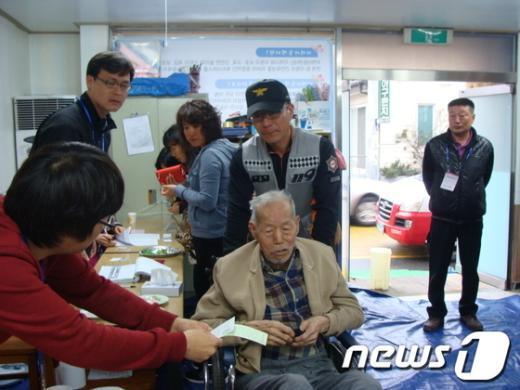 거동이 불편한 윤상보씨가 119구급대의 도움으로 투표에 참여하고 있다.  News1