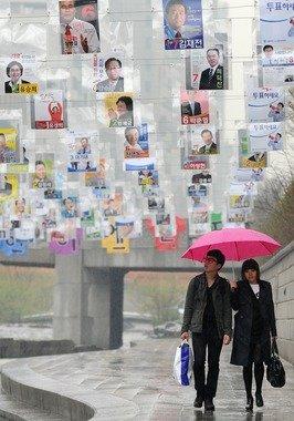 4.11총선을 하루 앞둔 10일 오후 서울 청계천 광통교 인근에서 시민들이총선 후보 포스터를 확인하며 발걸음을 재촉하고 있다.  News1 최진석 인턴기자