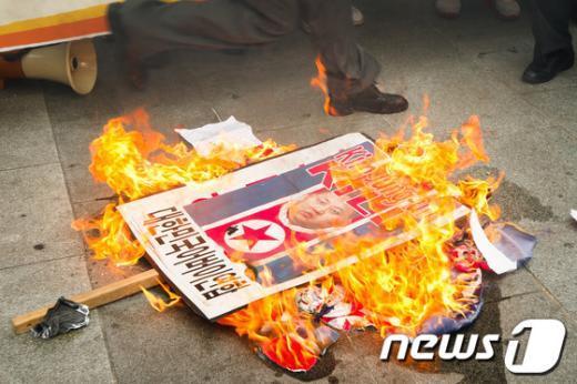 """북한이 장거리 로켓 은하 3호를 발사한 13일 오후 서울 광화문 KT사옥 앞에서 어버이연합 회원들이 북한의 미사일 발사를 규탄하는 기자회견을 열고 북한 인공기를 불태우는 퍼포먼스를 펼치고 있다. 조선중앙통신은 """"조선에서 첫 실용위성 광명성 3호 발사가 4월 13일 오전 7시 38분 55초 평안북도 철산군 서해위성발사장에서 진행됐다""""며 """"지구관측위성의 궤도 진입은 성공하지 못했다""""고 보도했다.  News1   유승관 기자"""