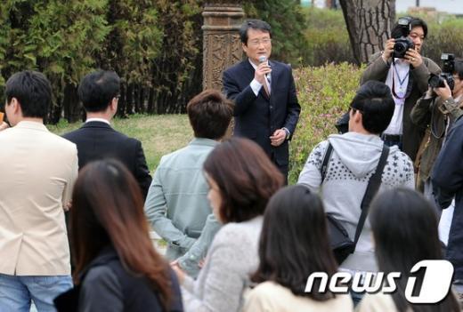 민주통합당 문성근 대표가18일 서울 여의도공원에서 마이크를 들고 한 시민의 질문에 답변하고 있다. 문 대표는이날 점심시간에 시민과의 대화시간을 가졌다.  News1 이종덕 기자