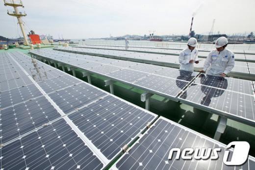 STX팬오션 관계자들이 'STX도브'호에 설치된 태양열 집열판을 점검하고 있다.  News1
