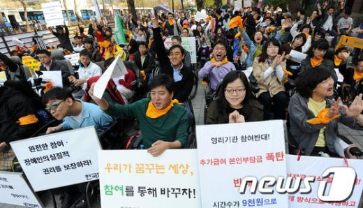 장애인의 날을 하루 앞둔 19일 오후 서울 여의도 이룸센터 앞에서 열린 '장애인총연합, 420장애인대회'에서 참가자들이 구호를 외치고 있다. News1 박지혜 인턴기자
