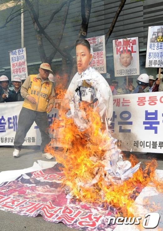 보수단체인 대한민국 어버이연합 회원들이 북한의 대남 협박을 규탄하며 김정은 모형을 불태우는 퍼포먼스를 펼치고 있다. News1 최진석 인턴기자