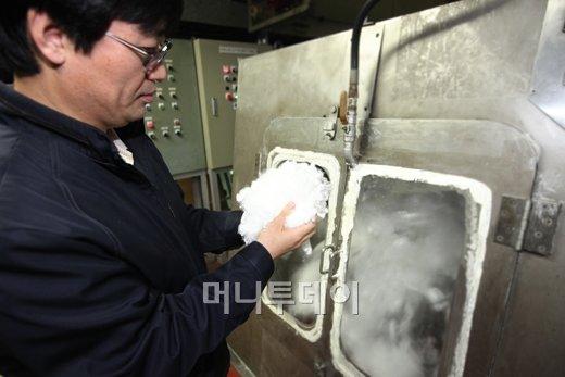 ↑휴비스 전주공장에서 생산된 폴리에스터 단섬유(LMF)를 검사하고 있다.