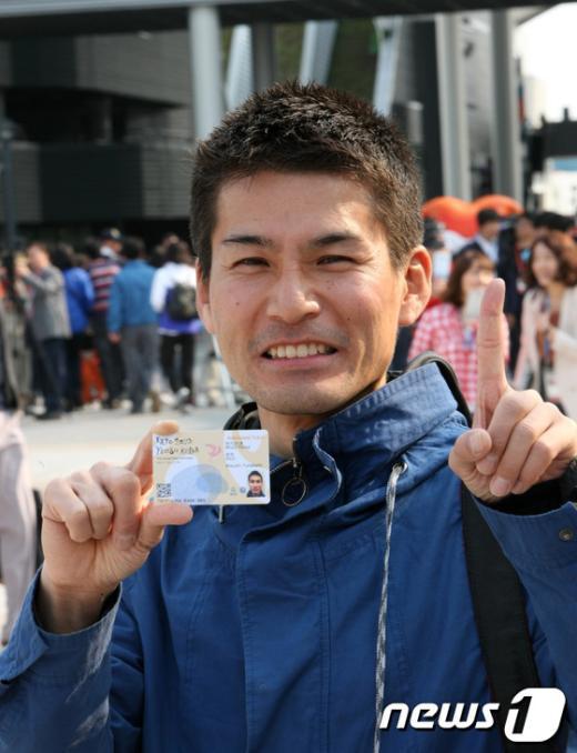 여수세계박람회 첫번째 입장객인 일본 오사카 출신 아스시 후타가미씨(39)가 박람회 전 기간 93일을 이용할 수 있는 입장권을 들고 환하게 웃고 있다./사진제공=조직위원회 News1