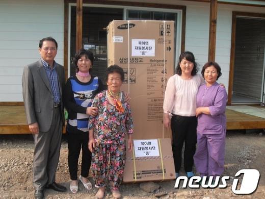 전남 장성군 북이면 여성자원봉사회가 화재로 실의에 빠진 주민에게 가전제품을 전달하고 있다./사진제공=장성군 News1