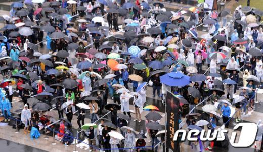 블리자드 엔터테인먼트의 디아블로3 출시를 하루 앞둔 14일 서울 성동구 왕십리 민자역사 비트플렉스 앞 광장에 한정판을 구매하기 위한 시민들이 우산을 쓰고 줄을 서 대기하고 있다. 2012.5.14/뉴스1  News1 양동욱 기자