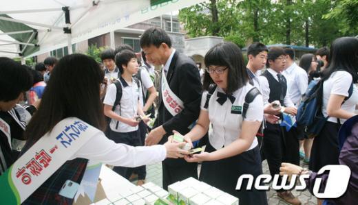 24일 경남 창원남산고등학교를 방문한 경남농협 직원들이 등굣길 학생들을 대상으로 주먹밥과 우유를 나눠주고 있다.(경남농협 제공)News1