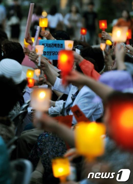 7일 저녁 서울 세종로 일민미술관 앞에서 한국시민단체협의회 주최로 열린 '종북세력 국회진출 저지를 위한 시민촛불문화제'에서 참가자들이 촛불을 들고 구호를 외치고 있다. 2012.6.7/뉴스1  News1   허경 기자