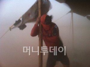 ↑김지산 기자가 모래폭풍에 맞서 천막 기둥을 붙들고 있다.(사진제공: 유지성)