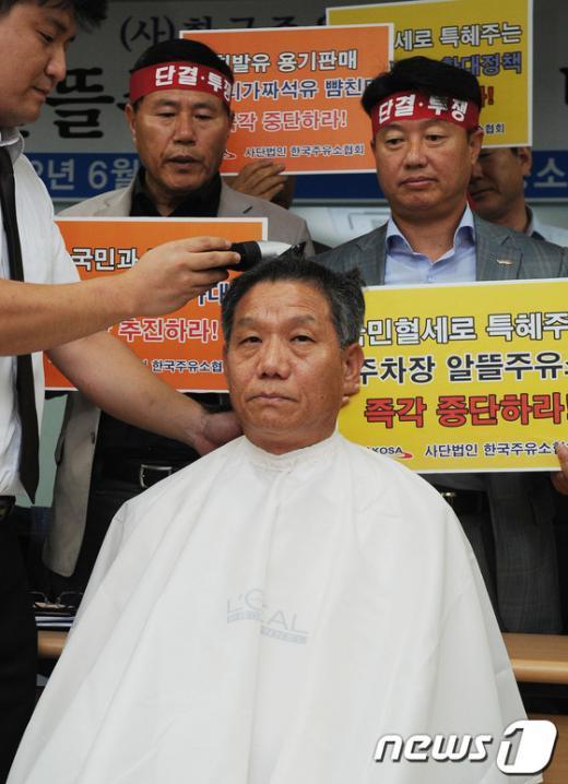 [사진]'알뜰주유소 반대', 머리카락 자르는 김문식 회장
