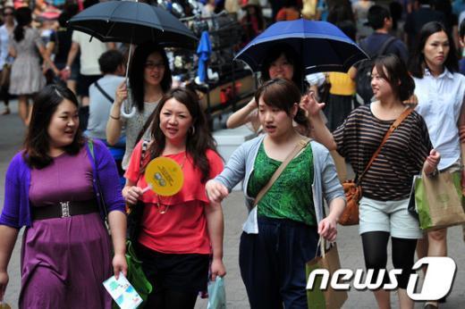 서울 명동에서 외국인 관광객들이 부채와 양산을 들고 걷고 있다.  News1 안은나 인턴기자