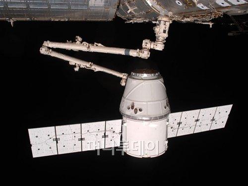 지난 5월 국제우주정거장의 로봇 팔이 우주선 '드래곤'을 움직이고 있는 모습. <출처:스페이스엑스>