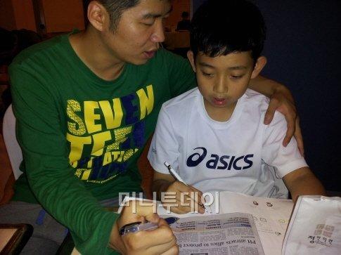 ▲ 서울대 멘토와 함께 현지 신문에 게재된 여수 엑스포 관련 기사를 읽고 있는 윤동욱(11·오른쪽)군