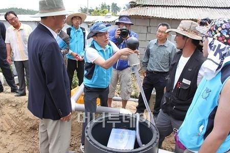 ↑한무영 서울대 교수(가운데)가 신안군 직원과 기도 주민들에게 빗물 탱크의 수질관리를 위한 '플로팅 석션' 을 설명하고 있다. 이것은 떠 있는 이물질이 있더라도 그 밑에 있는 깨끗한 물만 퍼내도록하는 장치다.ⓒ서울대 빗물연구소