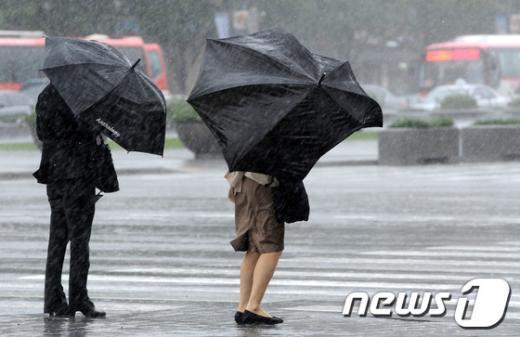 제16호 태풍 산바(SANBA)가 대구에 상륙해 내륙을 관통하고 있는 17일 오후 강풍과 함께 폭우가 쏟아지는 서울 세종로사거리에서 우산을 쓴 시민들이 발걸음을 재촉하고 있다.  News1 박세연 기자