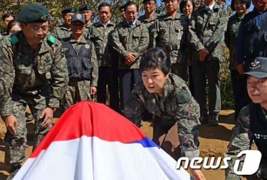 [사진]발굴 유해에 태극기 덮는 박근혜