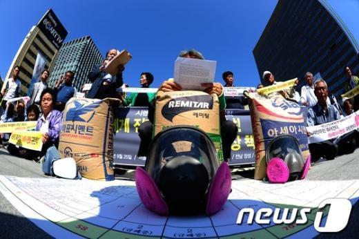 25일 오전 서울 광화문광장에서 열린 '시멘트산업 공해피해 전국대회' 기자회견에서 전국에서 올라온 시멘트 공장 인근 거주 공해피해 주민들이 피해대책을 촉구하는 퍼포먼스를 벌이고 있다. 2012.9.25/뉴스1  News1 한재호 기자