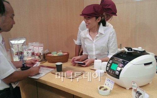 이달 초 열린 '2012 도쿄 인터내셔날 기프트쇼'에서 일본인 바이어가 리홈 효소현미밥솥에 대한 설명을 듣고 있다.