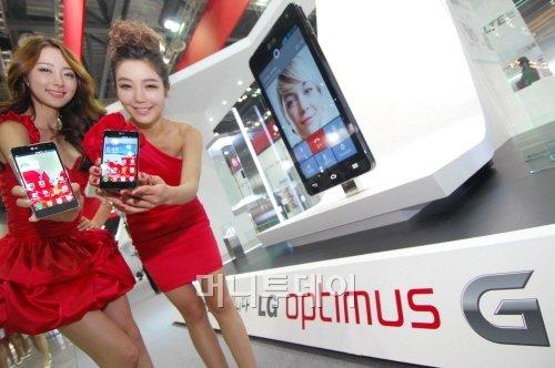 ↑LG전자가 9일부터 12일까지 경기도 일산 킨텍스(KINTEX)에서 열리는 한국전자전 2012(KES 2012)에서 1352㎡ 규모의 부스를 마련해 첨단 3D 및 스마트 기기를 대거 선보였다. 모델들이 LG전자 주력 프리미엄 스마트폰인 '옵티머스G'를 소개하고 있다. 이 제품은 세계최고 수준의 하드웨어 기반 위에 'Q슬라이드', '라이브 줌(Live Zooming)'등 실용적이고 독창적인 UX를 탑재했다.