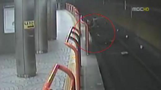 ▲의식을 잃은 할머니를 구하기 위해 선로로 뛰어드는 대학생 신상영 씨 (ⓒMBC 뉴스 영상 캡쳐)