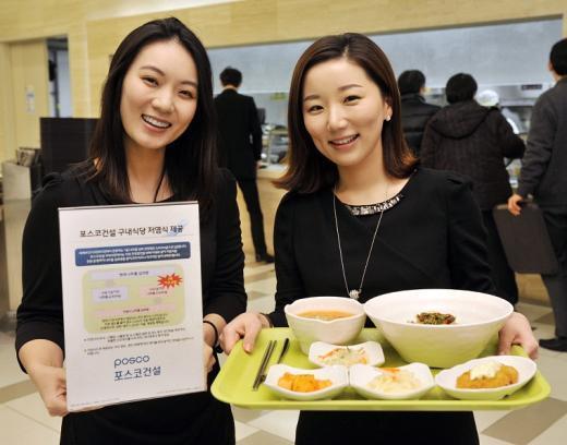 ↑포스코건설 구내식당에서 직원들이 저염식 식단을 들고 환하게 웃고 있다. ⓒ사진제공=포스코건설