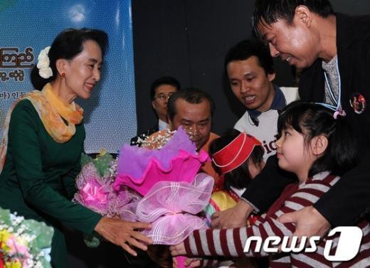 [사진]꽃다발 전달 받는 아웅산 수치